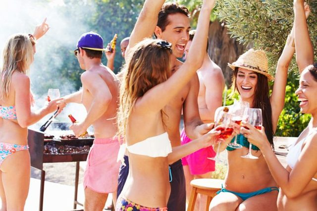 young people with drinks at a pool party