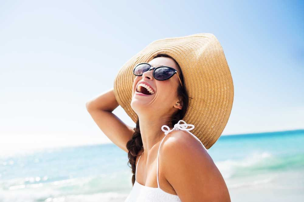 woman in sun hat, laughing at beach