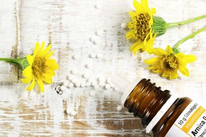 arnica flowers, bottle, and pills