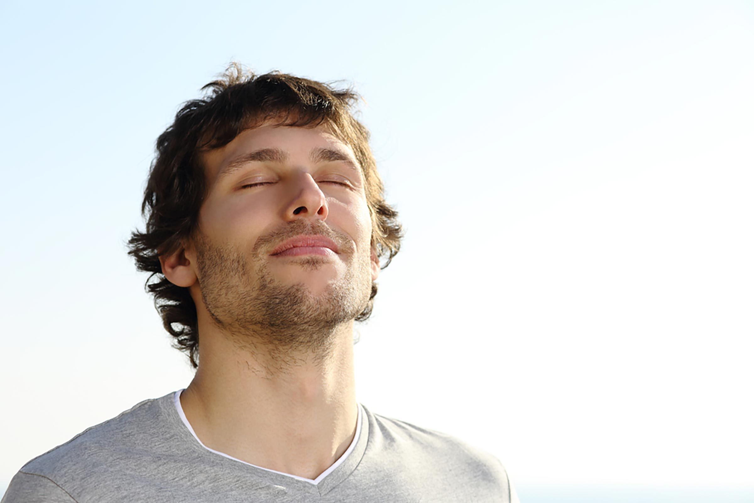man outdoors in the sun breathing deeply