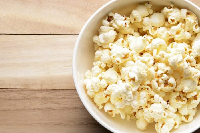 white bowl of popcorn on a wood surface