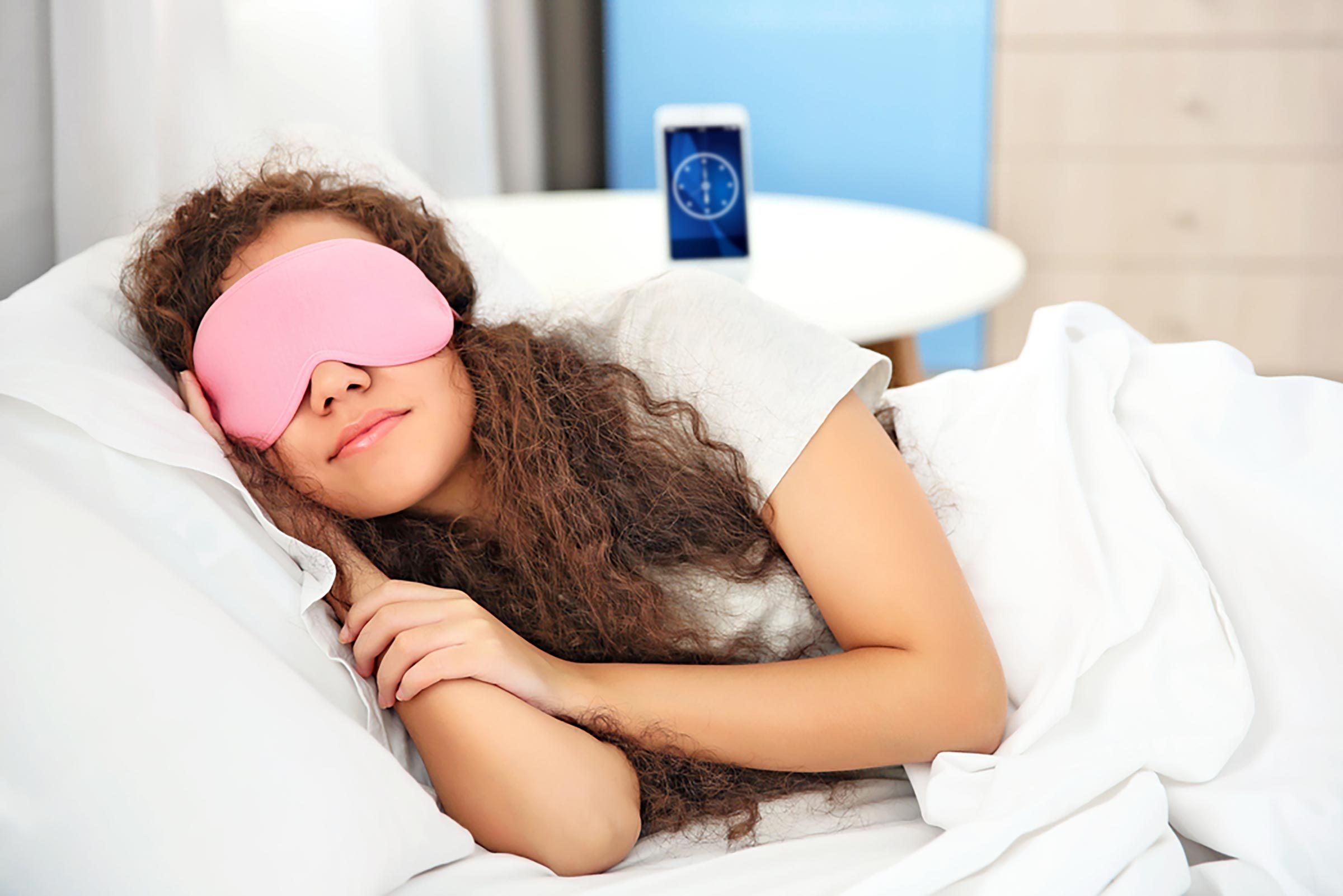 young girl in bed with sleep mask