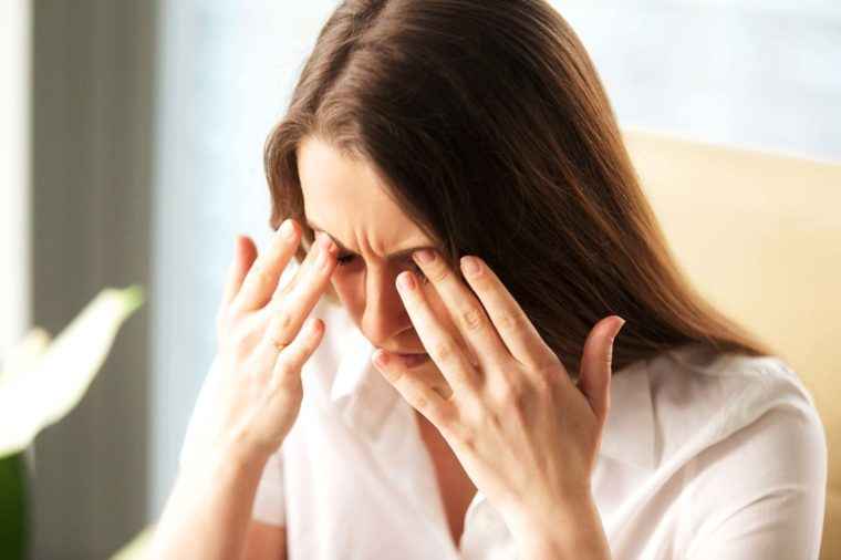 woman in pain pressing her hands into her eyebrows