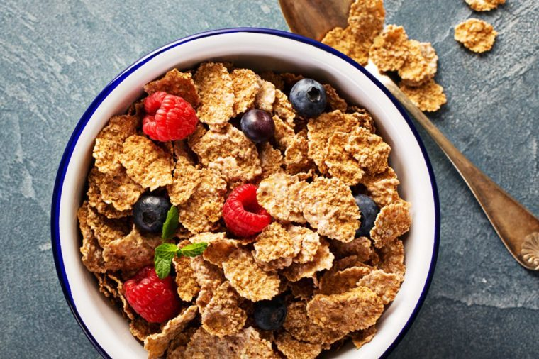 bowl of wheat cereal flakes with blueberries and raspberries