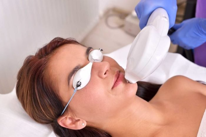 woman wearing eye protection being treated with pulsed light