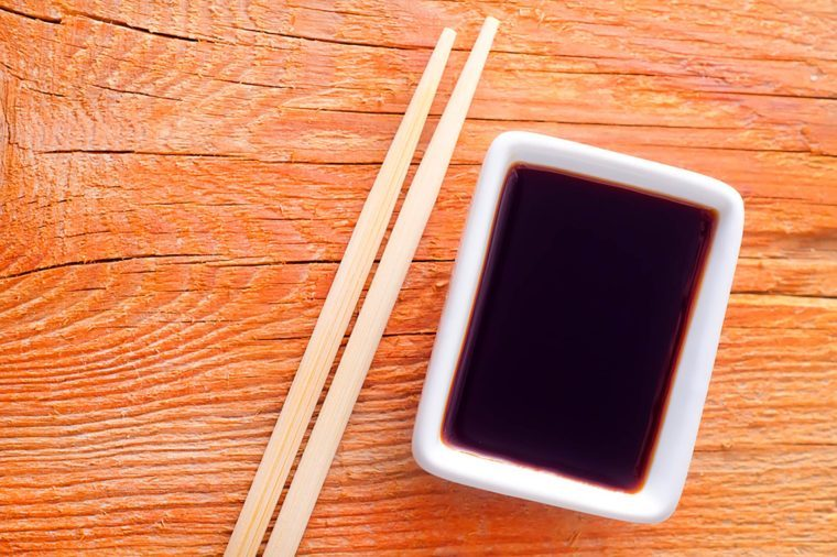 soy sauce in a white dish next to chopsticks on a wood table