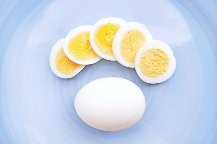 hard-boiled egg slices next to a whole hard-boiled egg