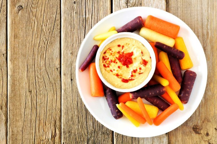 plate of various-colored carrots with bowl of hummus