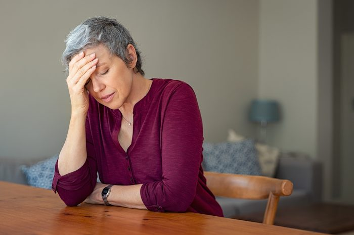 senior woman sitting at table with headache