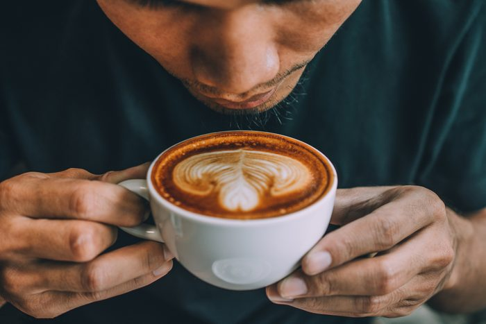 man blowing on cup of coffee