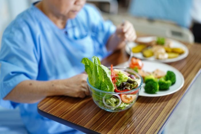 Asian senior or elderly old lady woman patient eating breakfast healthy food with hope and happy while sitting and hungry on bed in hospital.