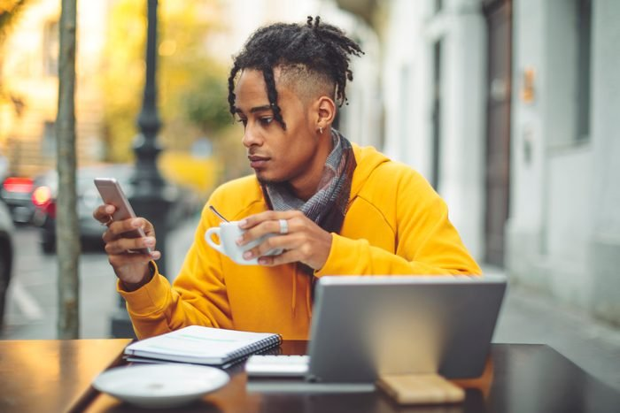 man sitting at cafe with laptop and cup of coffee