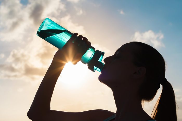 Woman drinking from bottle of water
