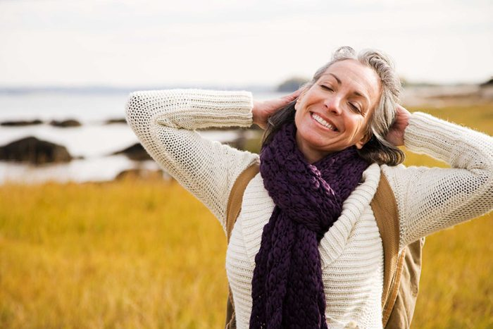 older woman smiling at the shore