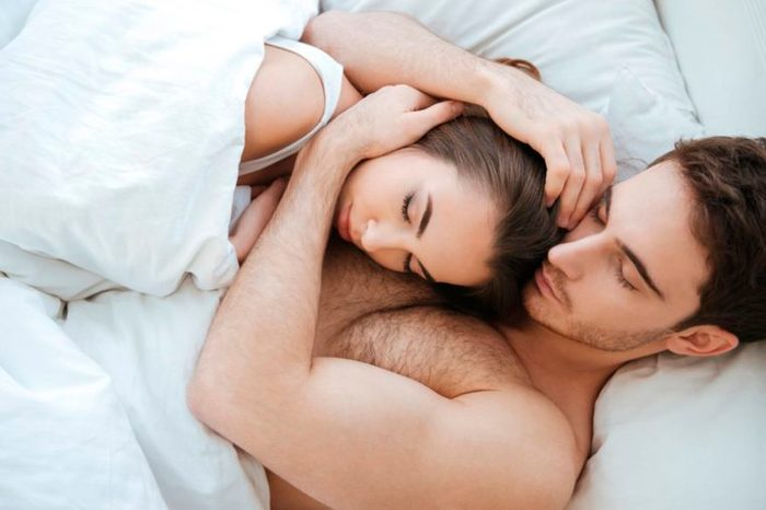 man embracing woman closely while they sleep