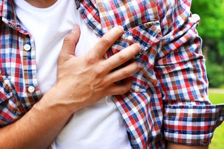 Man clutching his heart with his hand.