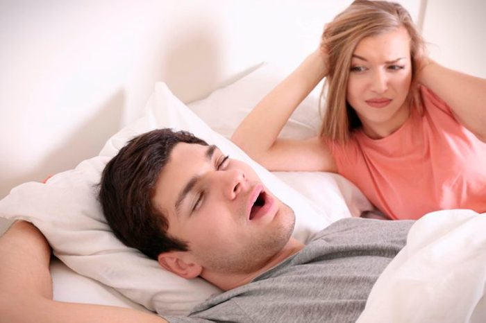 woman looks annoyed as man snores with mouth open