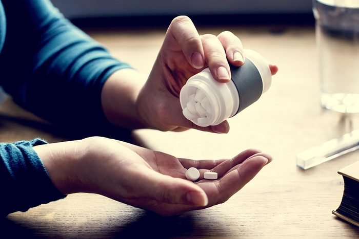 woman taking pills from pill bottle