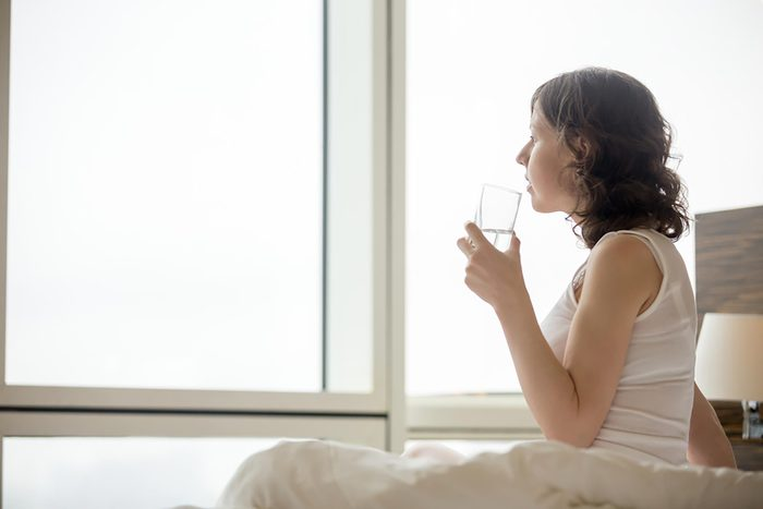 Woman sitting on edge of bed drinking glass of water