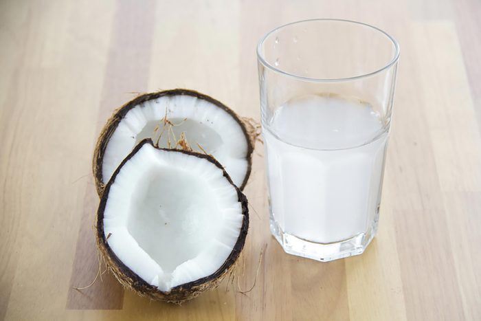 Glass of coconut water next to two halves of a coconut