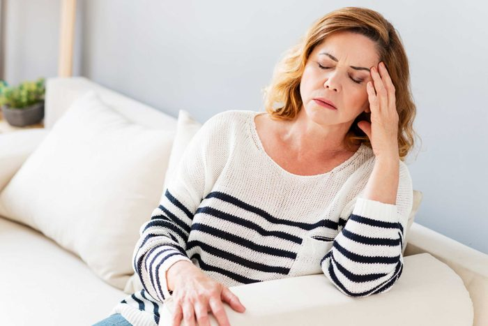woman on couch in pain, holding her head