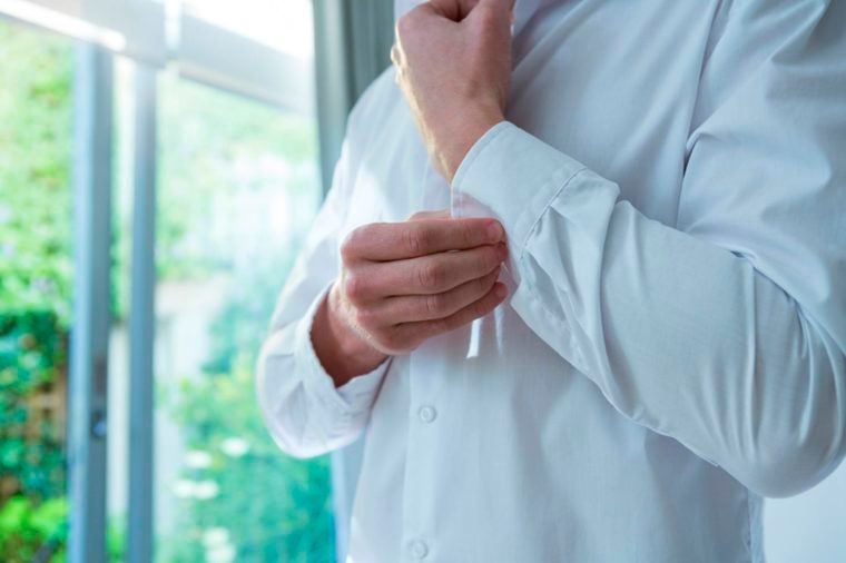 man buttoning sleeve of white shirt in morning sun