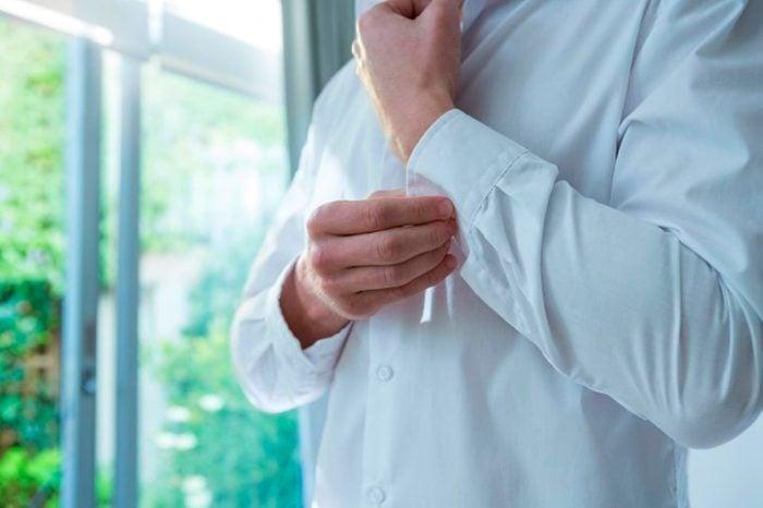 man buttoning sleeve of white shirt in morning sun
