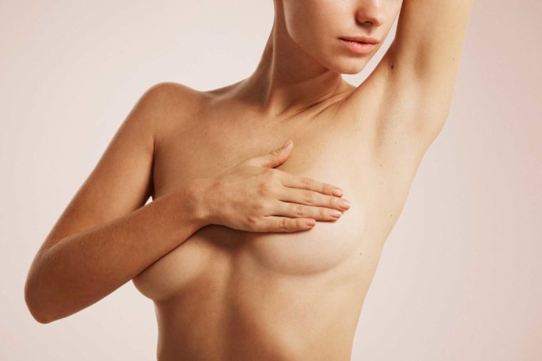 woman's naked torso with arm and hand covering breasts