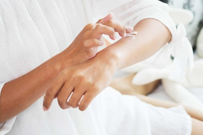 woman applying lotion to her arm