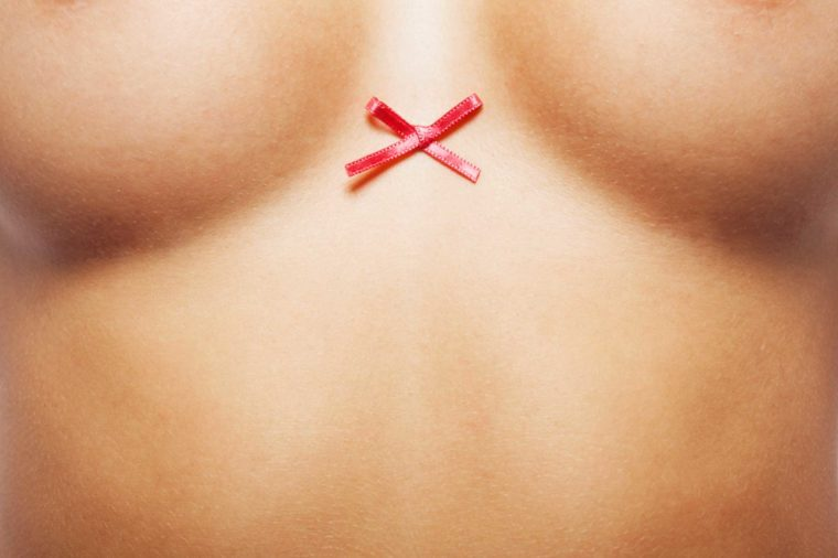 close up of woman's naked torso with cancer ribbon between breasts