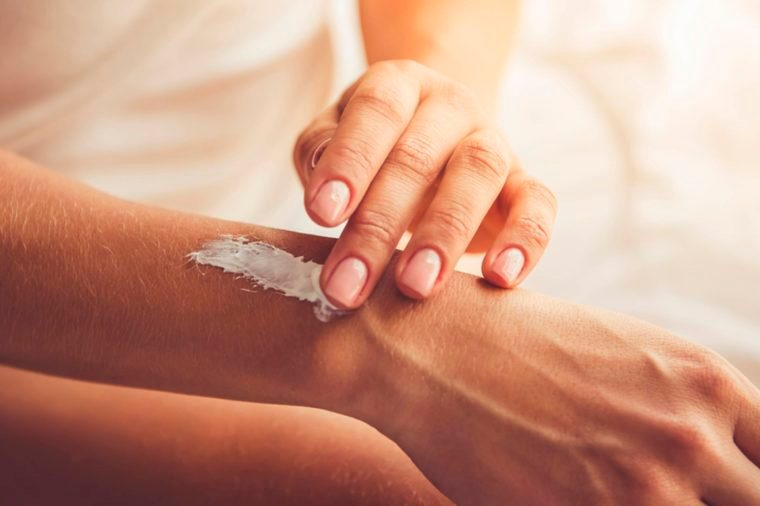 close up of a woman's hands as she applies lotion to her wrist