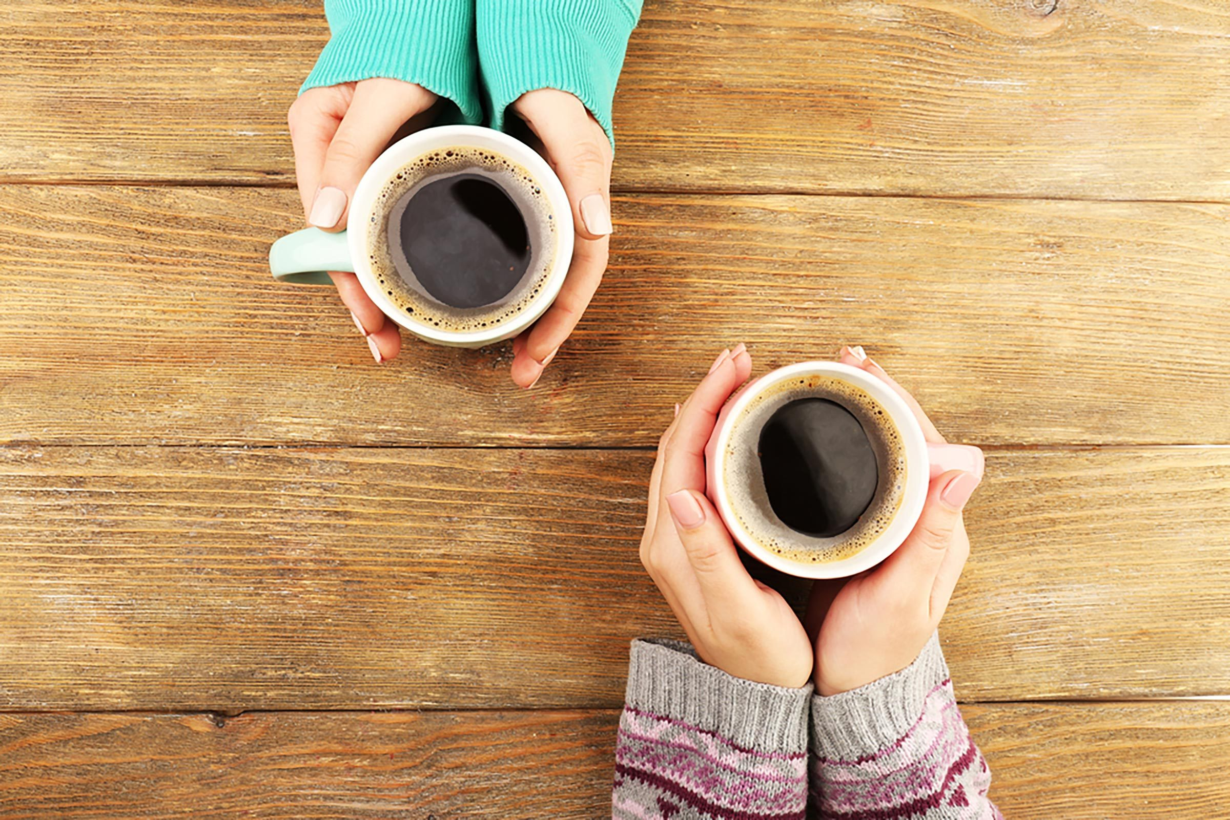 Two sets of hands holding cups of coffee