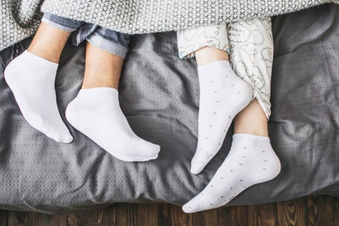 two sets of sock-clad feet peeking out of the bed covers