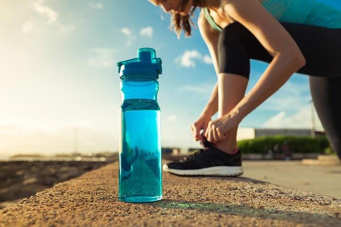 Woman runner tying sneaker next to bottle of water