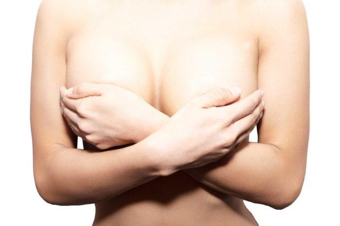Naked woman holding breasts , hands covering her nipples
