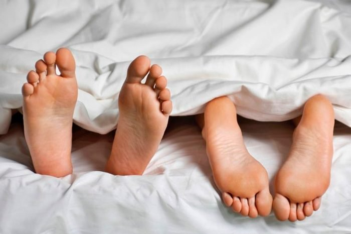 two sets of bare feet in a bed, one pointed up, the others down
