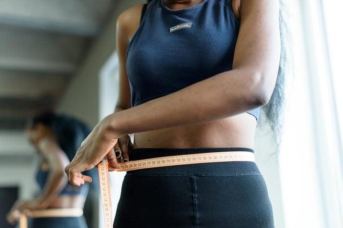 woman using tape measure on waistline