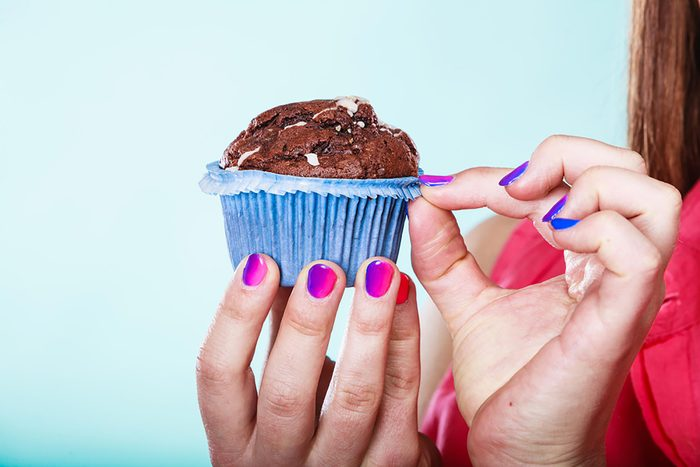 person unwrapping cupcake