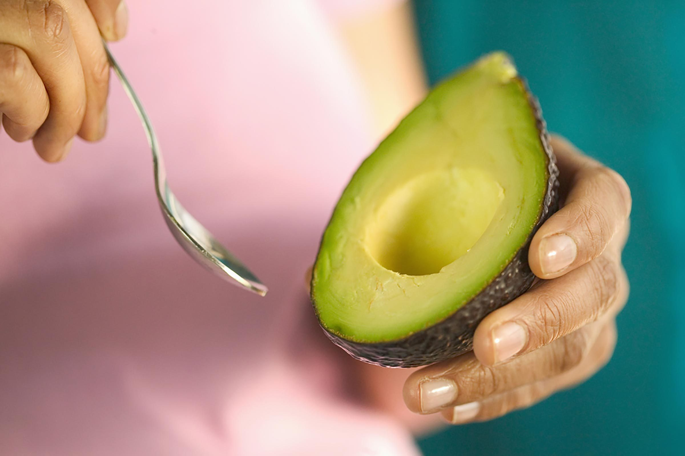 person eating avocado with spoon