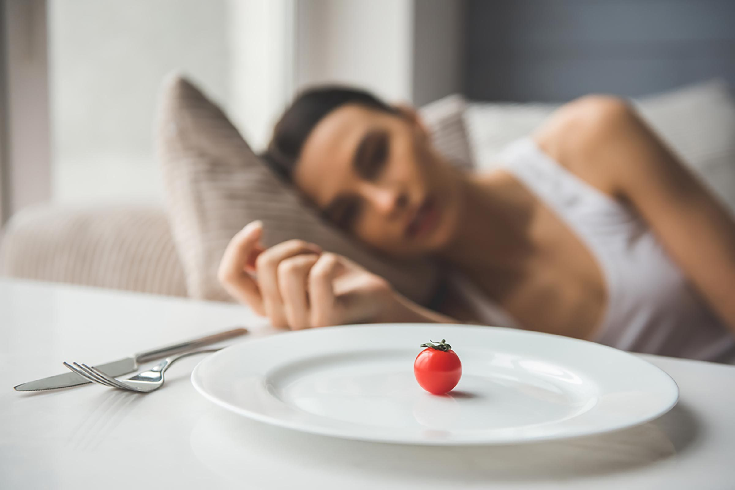 woman looking at tomato on plate
