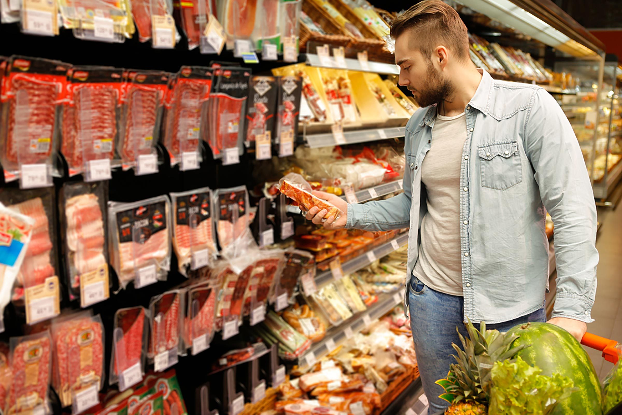 man reading food label in store