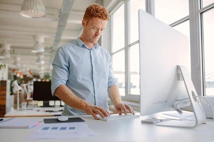 man standing at computer