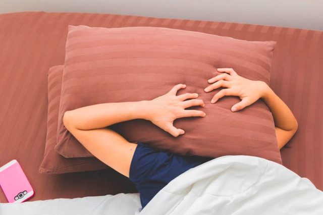 person holding pillow over their head