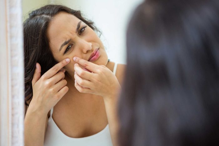 woman looking in mirror and popping a pimple