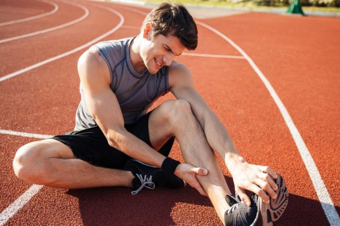 Man in workout gear stretching his leg as if having a cramp.