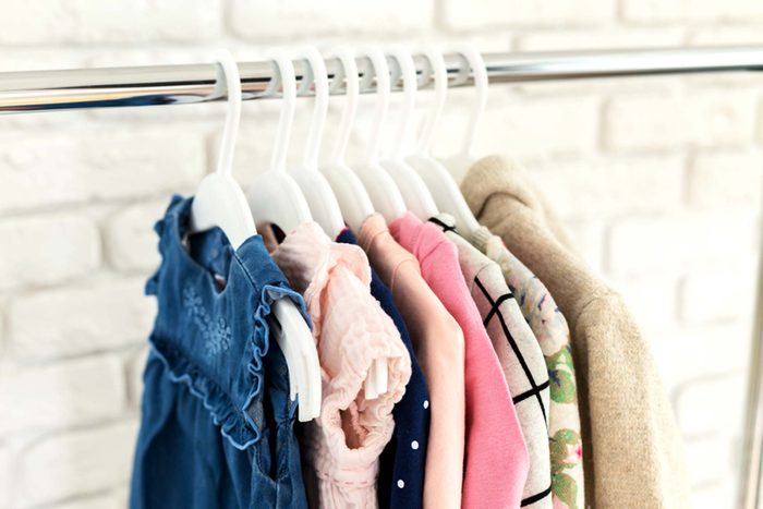 child's clothes hanging in closet