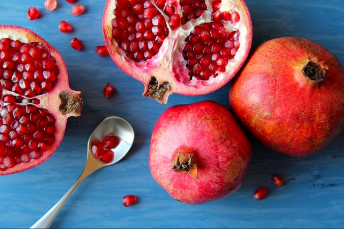 whole and halved pomegranate, spoon full of pomegranate seeds