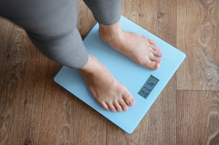 Woman in yoga pants weighing herself on a blue scale.