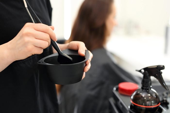 hair salon stylists mixing dye with girl in background