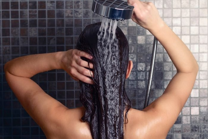 woman washing long hair in the shower